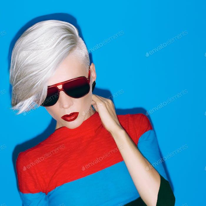 Mode blonde Dame mit trendigen Frisur und Sonnenbrille auf einem Blu