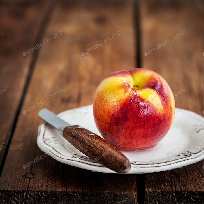 Fresh ripe peach on plate, wooden background