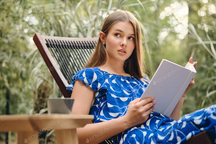 Young beautiful woman in blue dress dreamily reading book on wooden deck chair in park