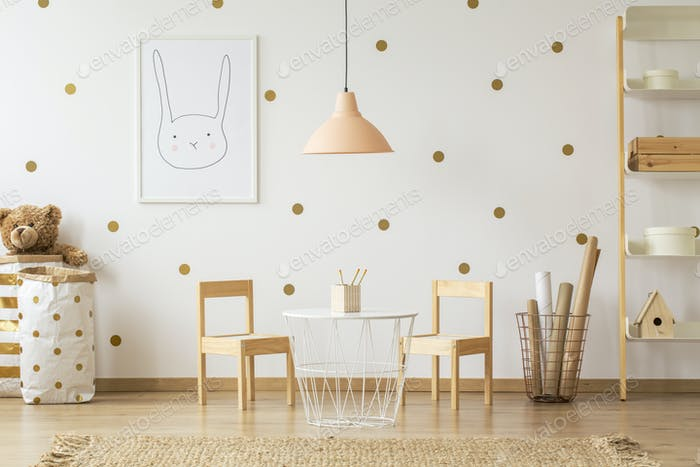 Pastel lamp above table between chairs in gold kid's room interi