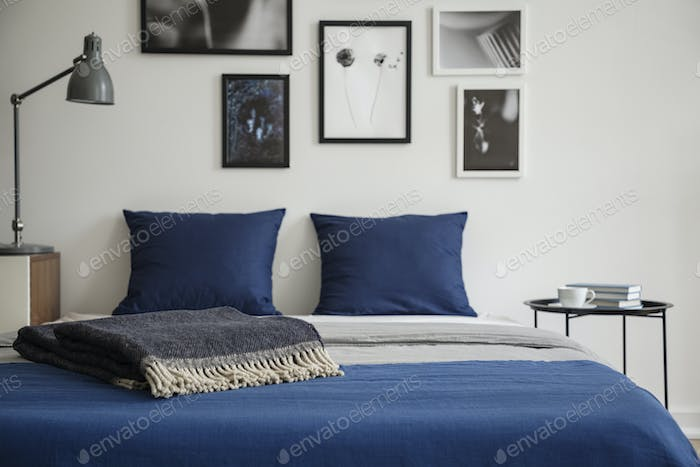 Close-up of bed with blue bedding and dark colored blanket. Beds