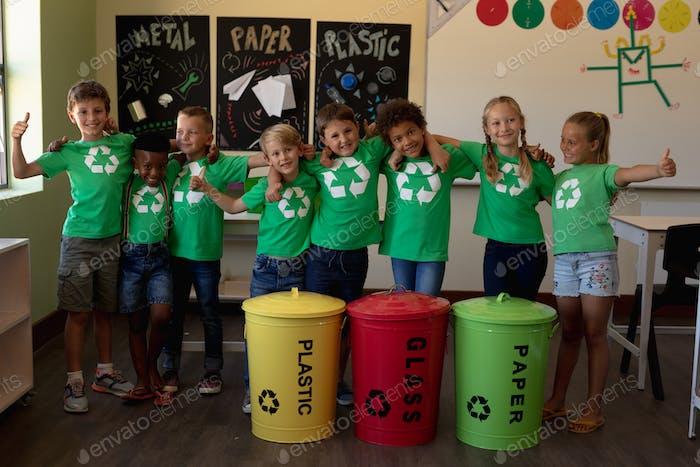Gruppe von Schulkindern, die farbcodierte Recyclingbehälter und -beutel in einer Grundschulklasse halten
