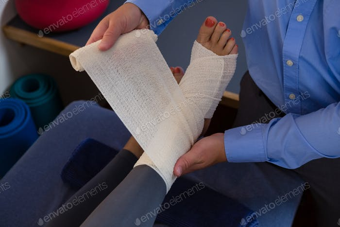 Physiotherapist putting bandage on injured feet of patient
