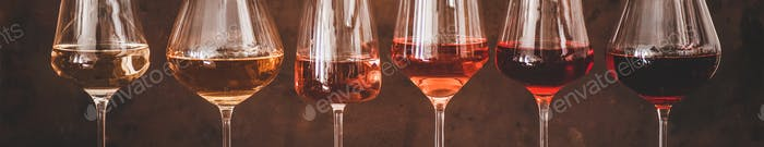Shades of Rose wine in glasses, rusty background, wide composition
