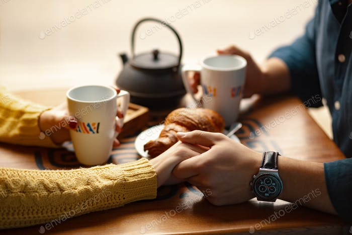 Young couple holding hands and cups with coffee