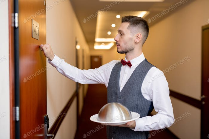 Young elegant waiter with food on cloche for one of guests knocking on the door