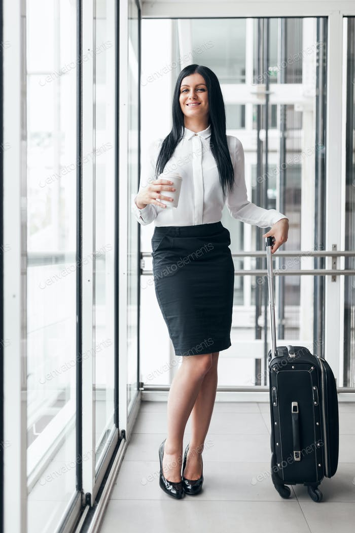 Successful business woman with coffee and suitcase in an office setting