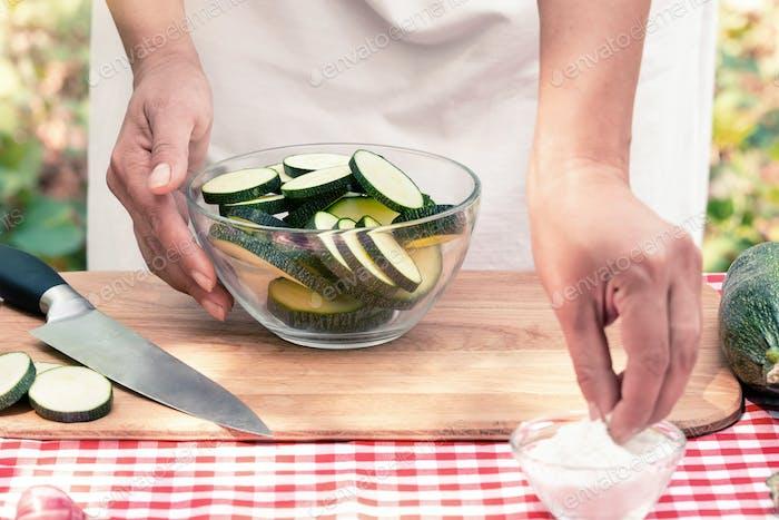 Weibliche Hände Salz geschnittene Zucchini auf einem Holzbrett