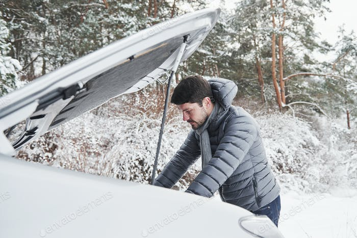 Guy stuck in the winter forest because his car have some problems. Tries to repair automobile