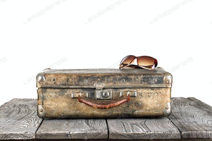 Vintage Koffer mit Sonnenbrille auf Holztisch
