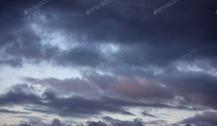 Dramatic magical sunrise cloudscape over blue gray color cloudy sky