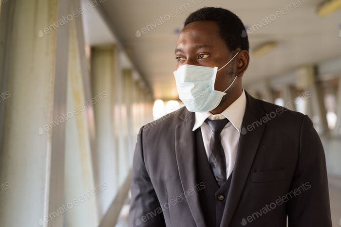 Portrait of African businessman with mask looking at view of the city at the footbridge