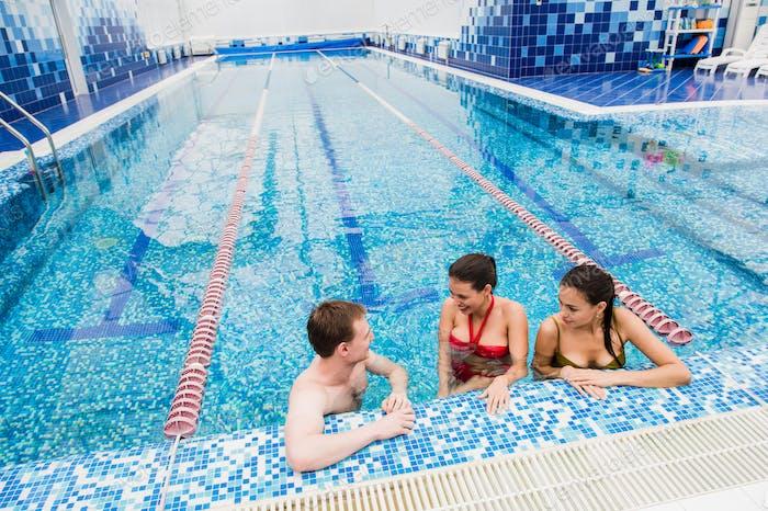 Young adults having fun talking in swimming pool indoors
