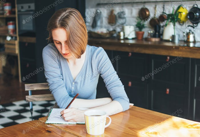 Young woman southpaw lefthender calculates family budget, writes in diary in kitchen