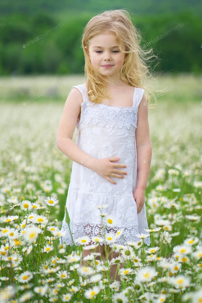 Little girl in camomile meadow.