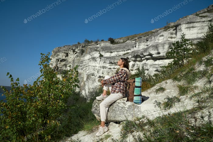 Female hiker with backpack sitting on rock