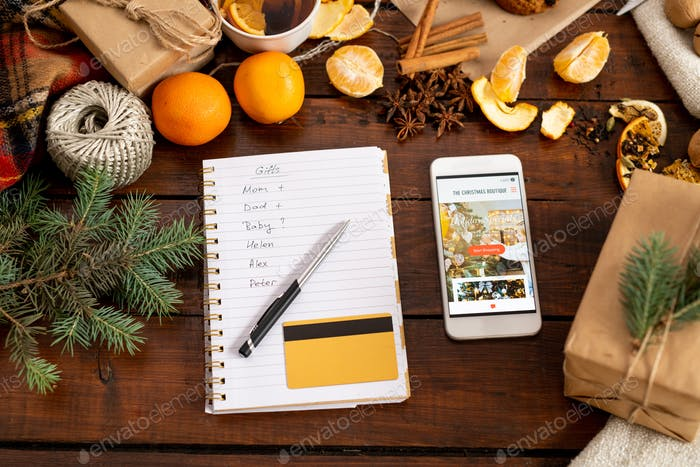 Smartphone with promo, notepad, penand credit card among xmas stuff on table