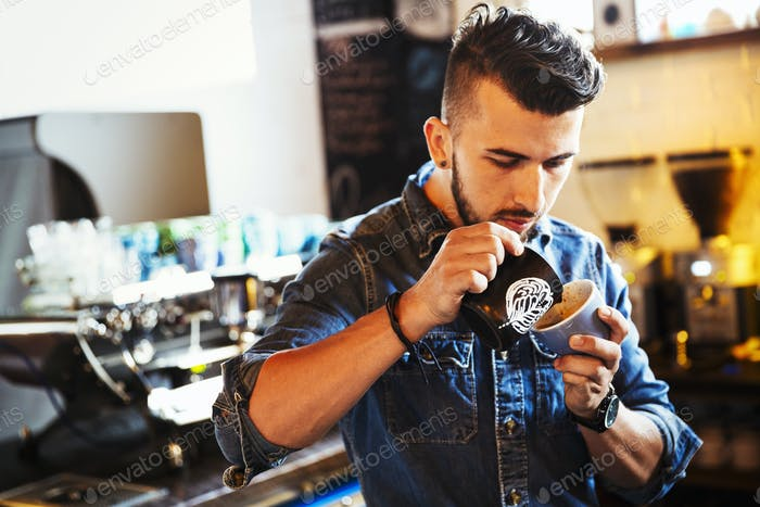 Specialist coffee shop. A man preparing capucchino creating froth patterns in a coffee cup.