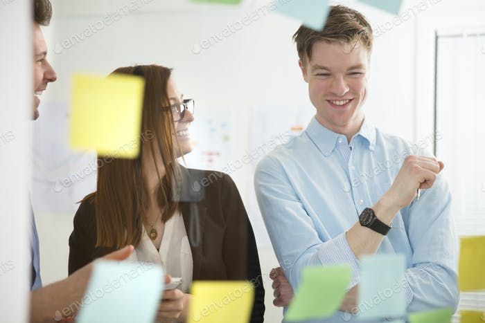 Business People Smiling In Office Seen Through Glass