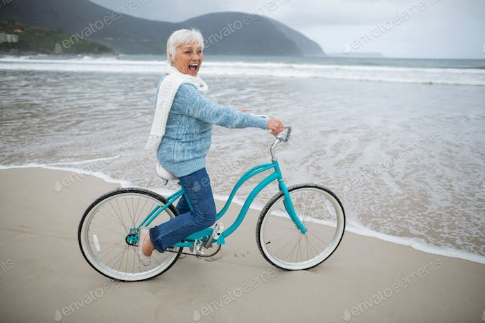 Senior woman riding bicycle on the beach