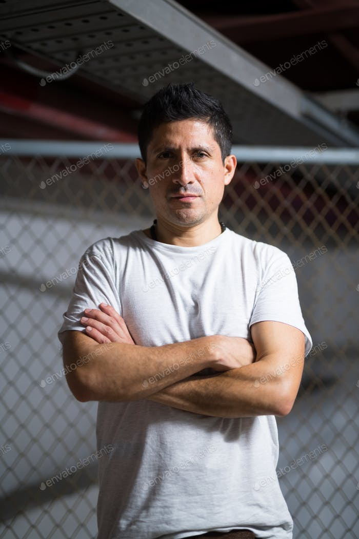 Hispanic man with arms crossed wearing casual clothing