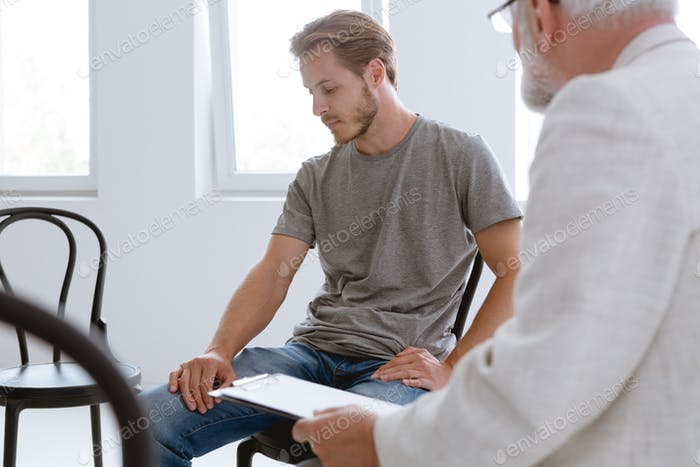Young handsome problematic patient during counseling with grey senior therapist