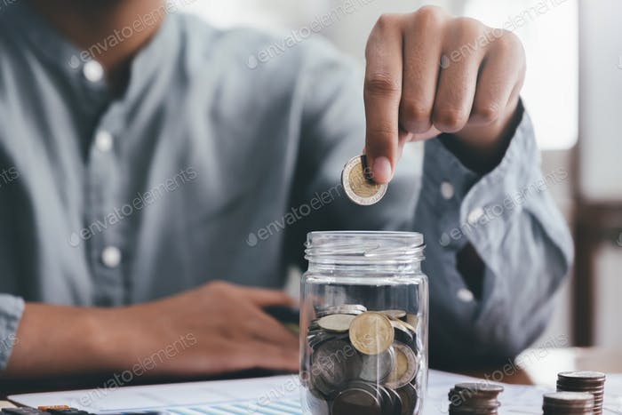 Closeup mano masculina sosteniendo monedas poniendo en vidrio.