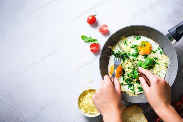 Mädchen Hände über Bratpfanne mit drei gekochten Eiern, Kräutern, Käse, Tomaten. Frau macht