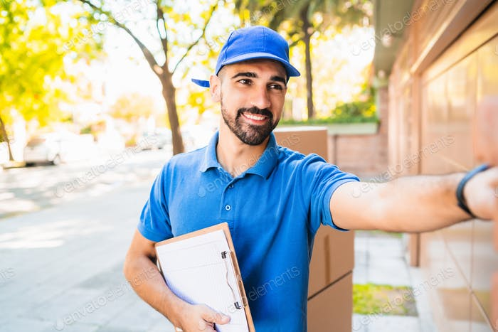 Delivery man carrying packages while making home delivery.