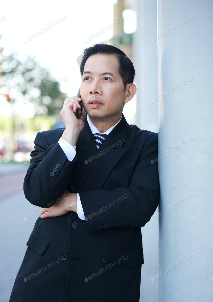 Businessman on mobile phone outdoors