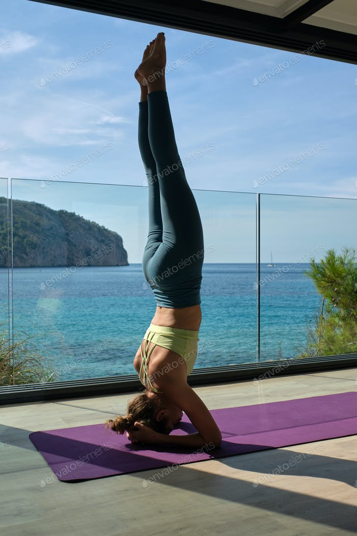 Woman doing Supported Headstand on balcony