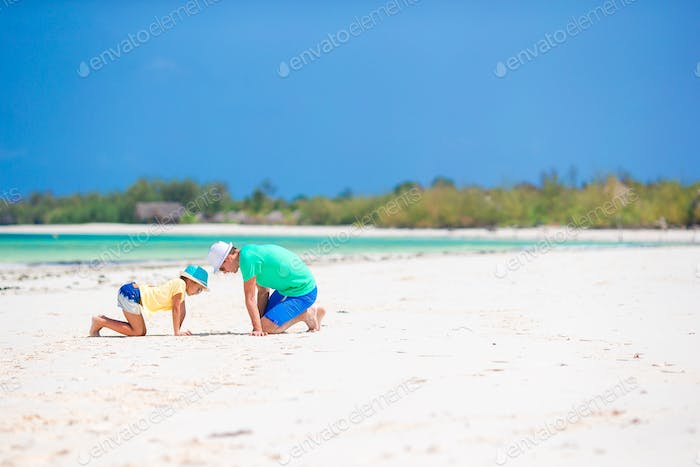Family of father and kid on white sandy beach