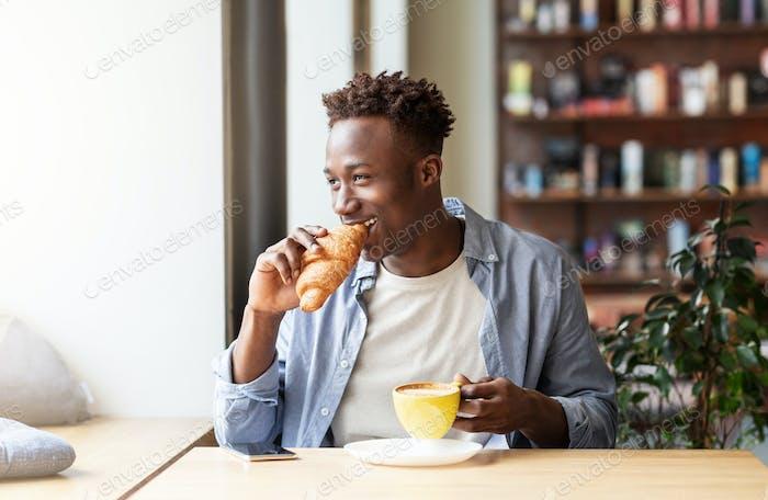 Funky Afroamerikaner Kerl mit Croissant mit Kaffee zum Mittagessen im Café