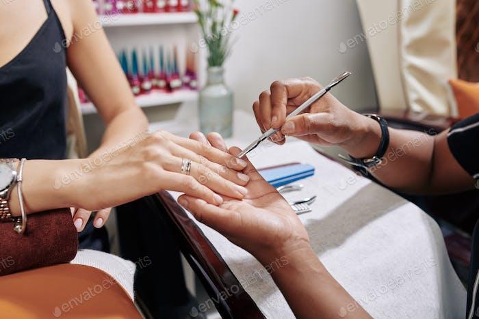 Manicurist pushing cuticle