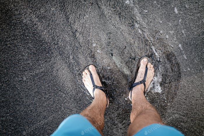 Man looking down at feet and sandals on volcanic black sand beac