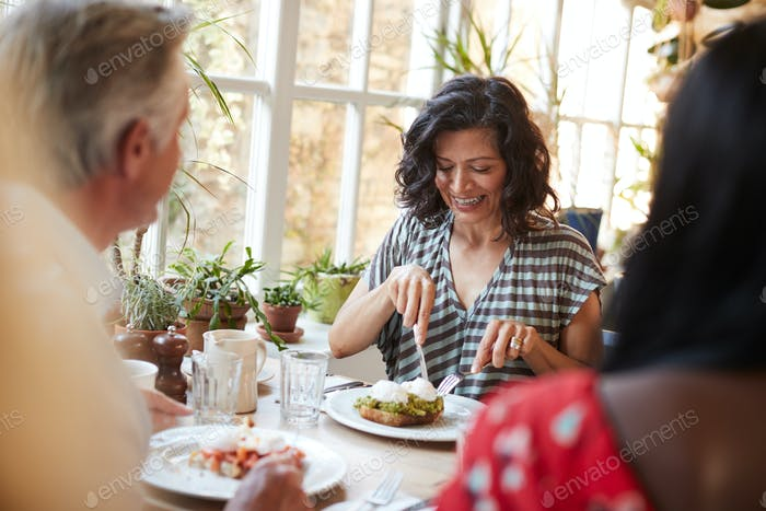 White adult woman eating with friends at a cafe, close up