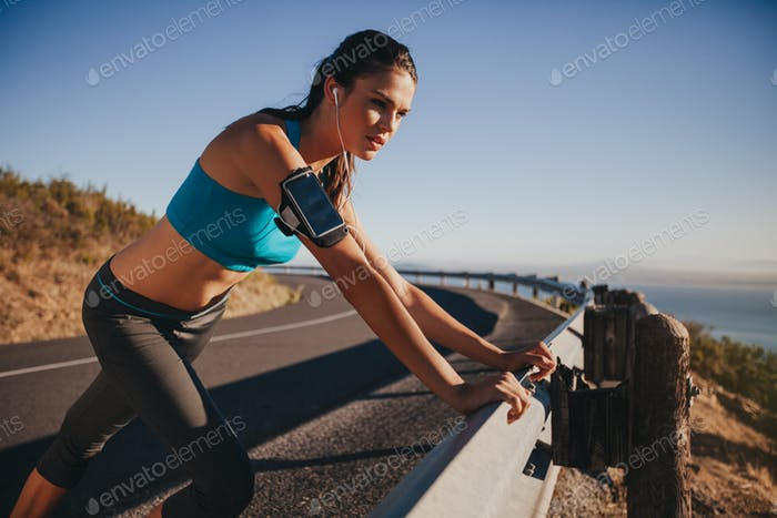 Young female athlete leaning on guardrail