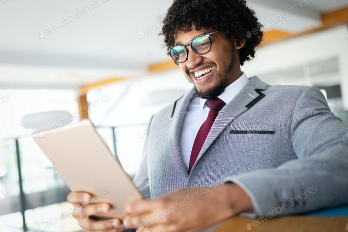 Handsome afro american businessman in classic suit is using a digital tablet