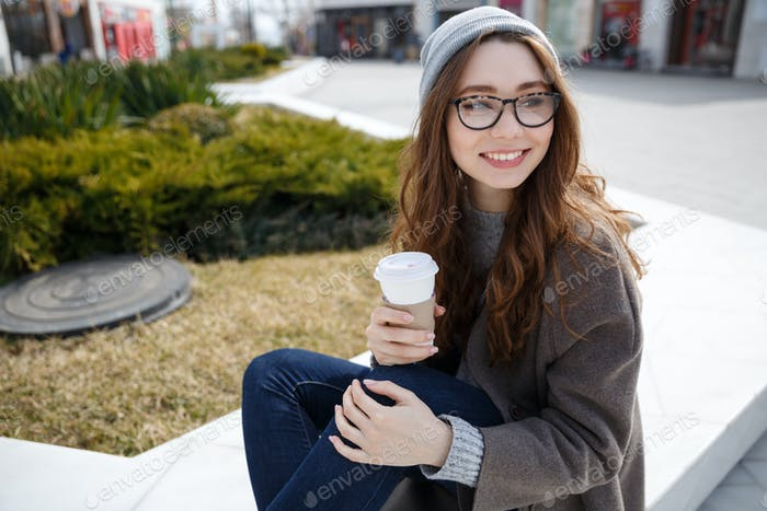 Happy woman in hat and glasses drinking coffee-to-go outdoors