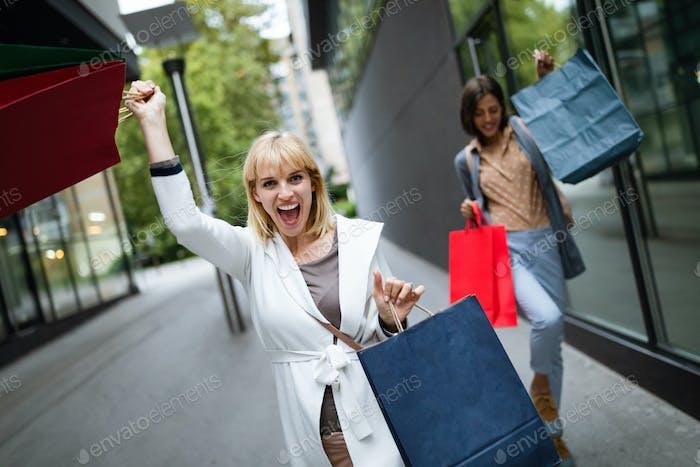 Beautiful happy women with shopping bags walking and having fun