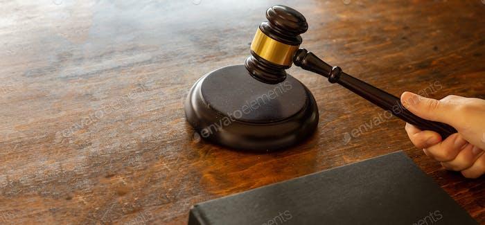 Judge hitting a gavel on wooden desk background. .