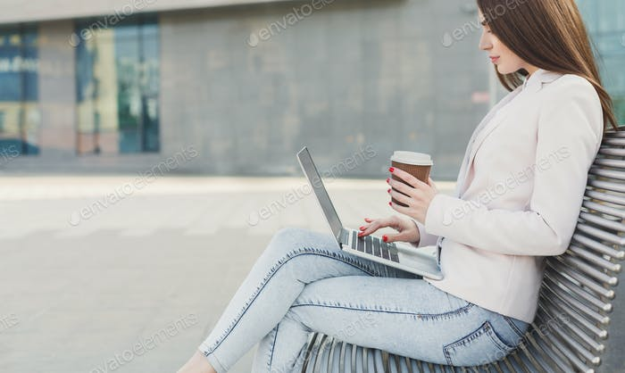 Caucasian businesswoman working with laptop outdoors