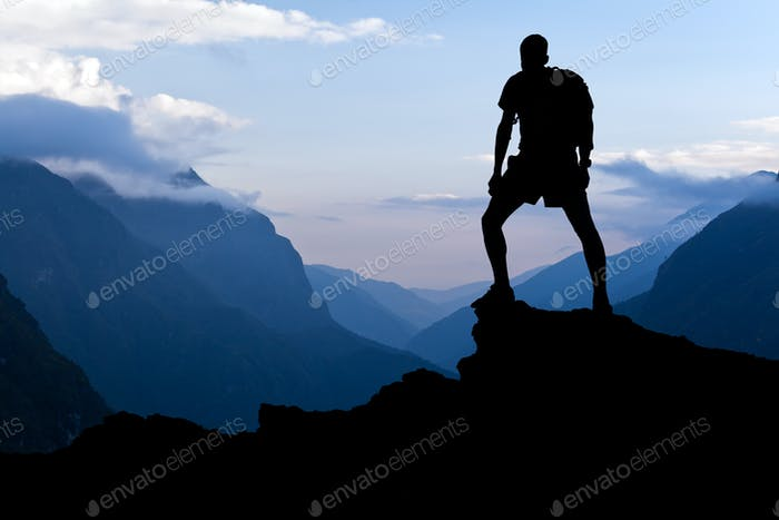 Man hiking success silhouette in mountains