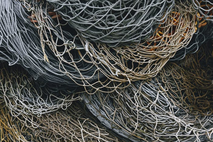 A heap of commercial fishing nets on the quayside.