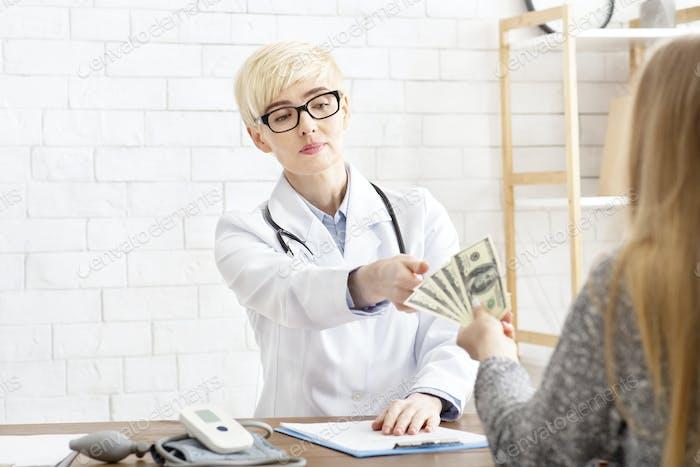 Soborno y corrupción en medicina. Dama seria doctora en gafas y bata blanca toma dólares de