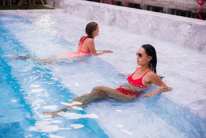 Young women relaxing on the swimming pool