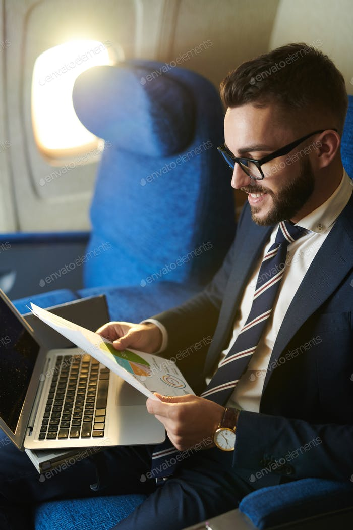 Young Businessman Working in Plane