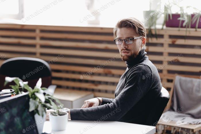Парень, одетый в повседневную офисную одежду, сидит в офисном кресле за столом в современном