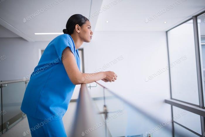 Nachdenkliche Krankenschwester lehnte sich auf Geländer
