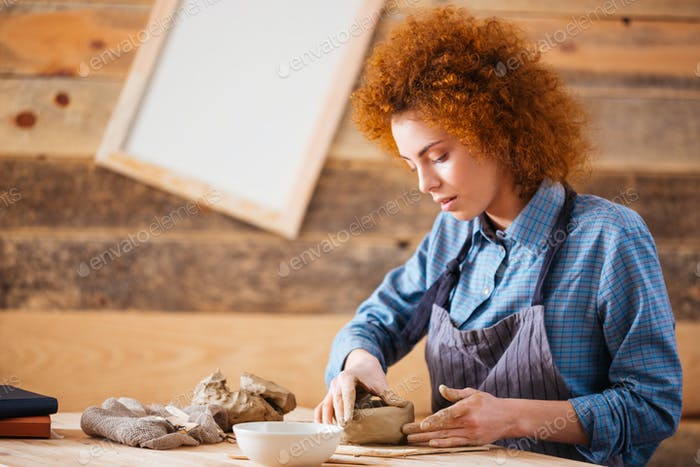 Creative young woman potter making earthen dishes in workshop